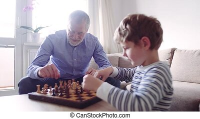 Senior grandfather with a grandson playing chess at home.