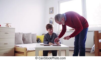 Senior grandfather with a small grandson at home drawing. -...