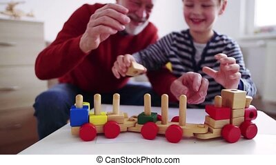 Senior grandfather with a small grandson at home playing. -...