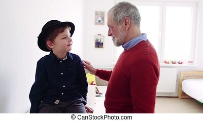 Senior grandfather with a small grandson at home, trying on a hat.