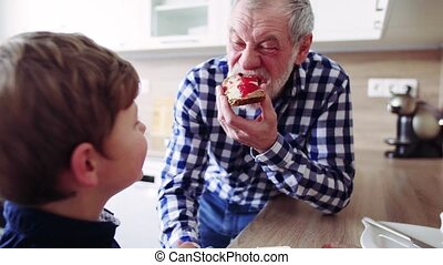 Senior grandfather with small grandson eating at home. -...