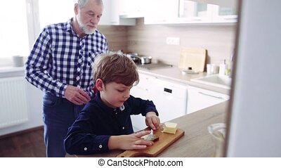 Senior grandfather with small grandson preparing food at...
