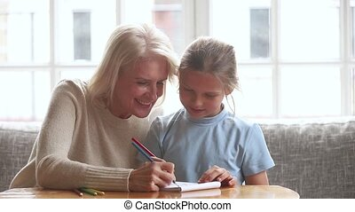 Senior grandma babysitter teaching little kid granddaughter...