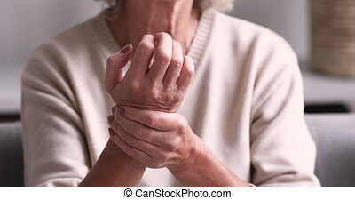 Senior grandmother massaging hand suffering from joint pain. Older woman having rheumatoid arthritis. Elder adult lady touching wrist feeling hurt. Osteoarthritis geriatric disease concept. Close up view
