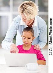 senior grandmother teaching grandchild computer