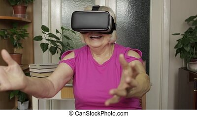 Senior grandmother woman in virtual headset glasses watching...