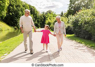 senior grandparents and granddaughter at park - family,...