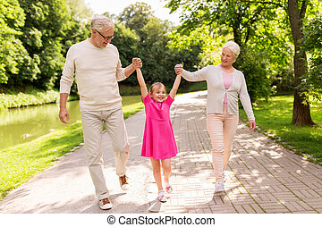 senior grandparents and granddaughter at park