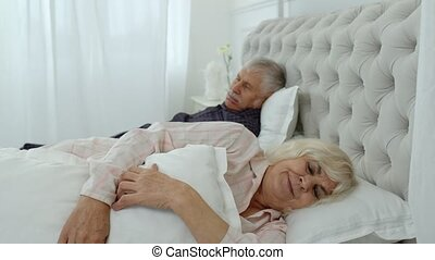 Senior Caucasian grandparents couple lying and sleeping in bed at home. Irritated woman getting disturbed with man loudly snoring. Grandmother covering her ears with pillow while grandfather snores