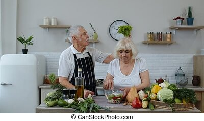 Senior grandparents in kitchen. Funny grandpa joking on grandma. Putting a lettuce about her head