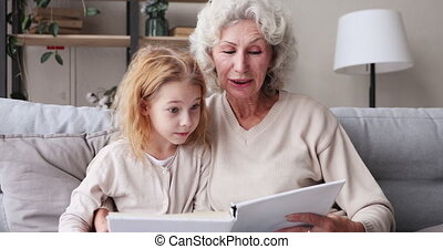 Senior granny reading book hugging granddaughter sitting on ...