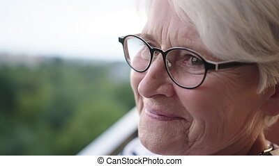Senior gray haired woman with glasses standing alone on the balcony with smile but sad eyes. High quality 4k footage