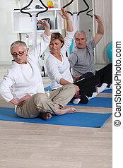 Senior group doing fitness indoors