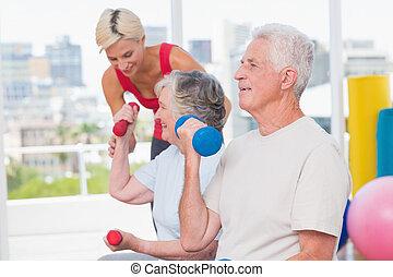 senior, gy, pomagając, trener, znowu, podnoszenie, człowiek, dumbbells, kobieta