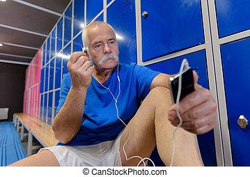 senior gym goer putting his headset