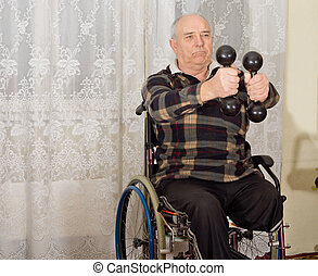 Senior handicapped man exercising with a pair of dumbbells...