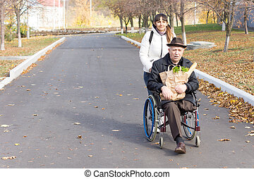 Senior handicapped man with a female carer being pushed...