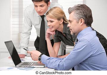 senior, handlowiec, pokaz, coś, na, laptop., posiedzenie razem, z, grupa handlowych ludzi, w, nowoczesny, biuro