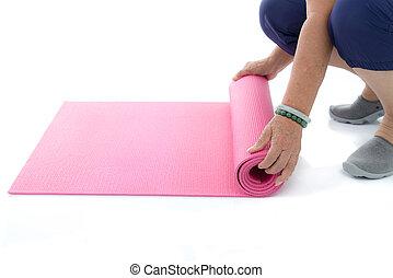 Senior hand's rolling pink yoga mat on white.