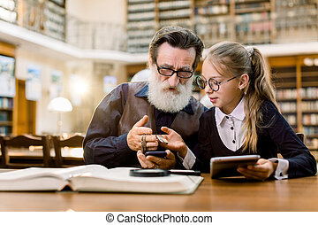 Senior handsome bearded man and his pretty granddaughter looking at a vintage clock on a chain, while sitting at the table with books, tablet and phone in old ancient library.