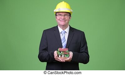 Senior handsome businessman as engineer holding house...