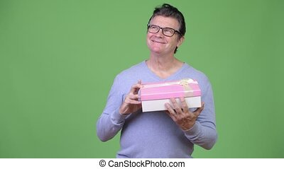 Senior handsome man opening gift box