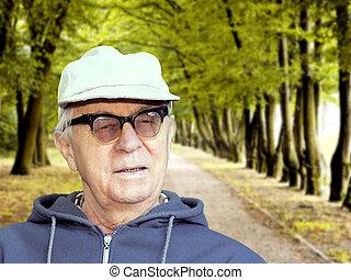 Senior happy man sitting in the park