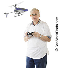 A senior man flying his RC helicopter. Focus on helicopter. Motion blur on propellers. On a white background.