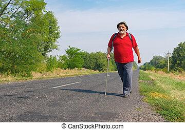 Senior hiker walking on a roadside in Ukrainian rural area