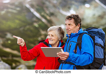 Senior hikers couple with tablet - Senior hiking couple...