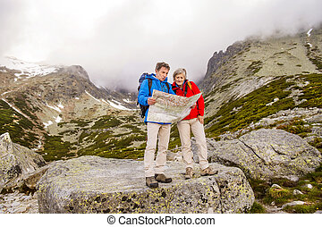 Senior hikers with map - Senior hikers couple looking at the...