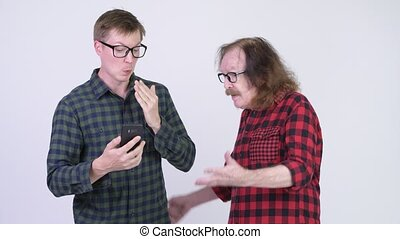Senior hipster man catching young hipster man using phone...
