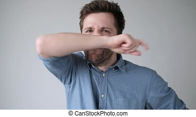 Senior hispanic man has running nose, rubs nose with hand, being ill, caught cold on rainy weather. Unhygienic habbit.
