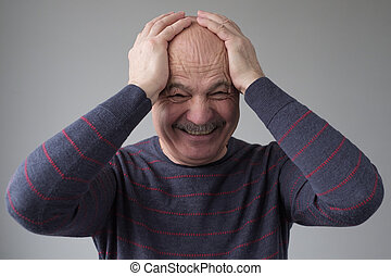 Senior hispanic man laughing out loud with closed eyes and hand on his head