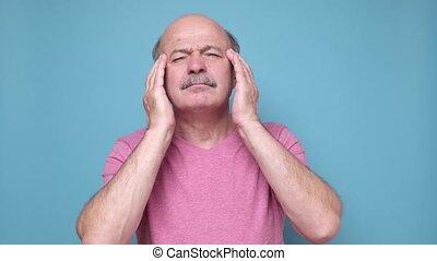 Senior hispanic man suffering from headache feeling ...