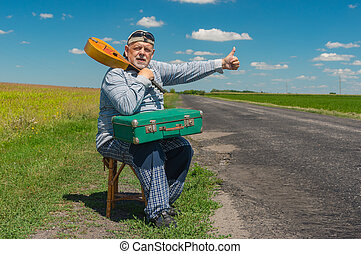 Senior hitch-hiker having short rest on a rural roadside with an ancient green suitcase and mandolin