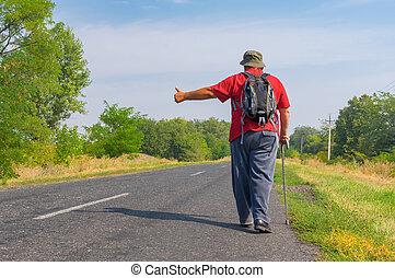 Senior hitchhiker walking on a roadside in Ukrainian rural area