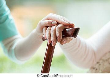 Senior holds hands on walking stick