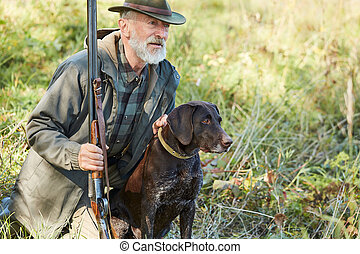 Senior hunter with dog in forest