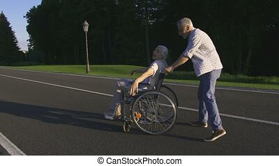 Senior husband spinning wife on wheelchair in park