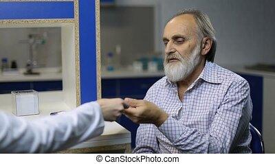 Senior ill patient checking temperature at clinic