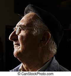 Senior in cap and eyeglasses sideview