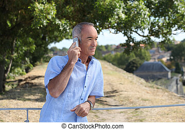 senior in the country talking on his cell phone