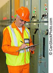 senior industrial technician taking machine readings
