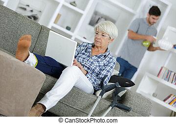 senior injured woman using laptop
