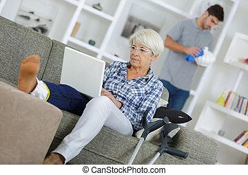 senior injured woman with laptop