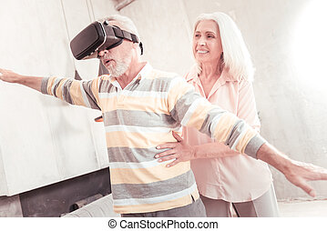 Senior interested man standing and looking through the VR ...