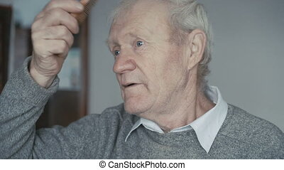 Senior is combing his short gray hair with a wooden comb 4K
