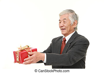senior Japanese businessman offering a gift