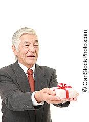 senior Japanese businessman offering a gift